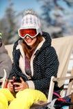 Meisjeszitting bij ligstoelen in de winter bergen en binnen het ontspannen Stock Afbeelding
