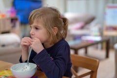 Meisjeszitting bij ontbijt die muesli met yoghurt van witte kom eten royalty-vrije stock foto