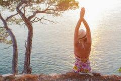 Meisjeszitting bij zonsondergang met omhoog handen Stock Fotografie