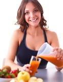 Meisjeszitting in de keuken op het bureau met fruit en glazen met sap Stock Fotografie