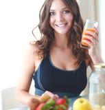 Meisjeszitting in de keuken op het bureau met fruit en glazen met sap Stock Foto