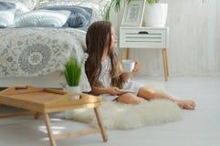 Meisjeszitting in de ochtend dichtbij het bed met een weg kop thee en blikken royalty-vrije stock fotografie