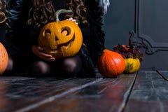 Meisjeszitting dichtbij de Halloween-lantaarn van de pompoen hoofdhefboom op dar Royalty-vrije Stock Afbeeldingen