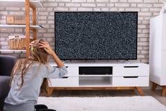 Meisjeszitting dichtbij Televisie zonder Signaal stock afbeelding