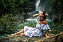 Meisjeszitting door de waterval stock afbeeldingen