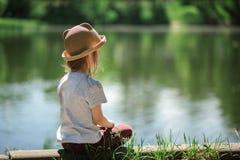 Meisjeszitting door het meer stock afbeeldingen