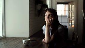 Meisjeszitting in en koffie die, die uit het venster in langzame motie glimlachen kijken stock footage