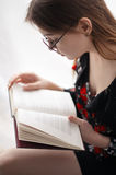 Meisjeszitting en lezing Royalty-vrije Stock Foto's