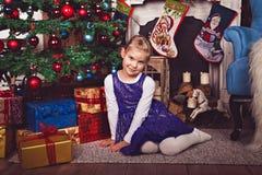 Meisjeszitting in Kerstmisruimte stock foto