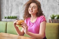 Meisjeszitting in koffie, holdings smakelijke hamburger, het glimlachen royalty-vrije stock afbeeldingen