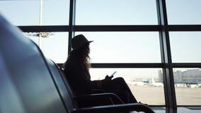 Meisjeszitting in luchthaven stock videobeelden