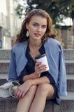 Meisjeszitting met een document kop van koffie royalty-vrije stock foto