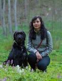 Meisjeszitting met hond op weide Royalty-vrije Stock Afbeeldingen