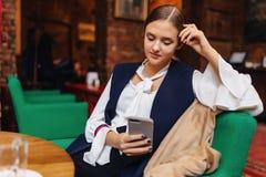 Meisjeszitting met telefoon in koffie royalty-vrije stock foto