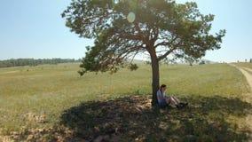 Meisjeszitting onder een boom, die in de schaduw rusten, die iets in het album trekken stock footage