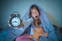 Meisjeszitting op bed wakker in het midden van de en nacht die rusteloos met slapeloosheid geeuwen voelen stock fotografie
