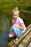 Meisjeszitting op de bank van een vijver Royalty-vrije Stock Fotografie