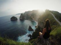Meisjeszitting op de ertsader terwijl de zonsondergang, het overzees en het strand, Bali, Indonesië bekijken Stock Afbeeldingen