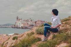 Meisjeszitting op de heuvel met overzeese en stadsachtergrond stock fotografie