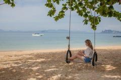 Meisjeszitting op de schommeling op het tropische strand Stock Fotografie
