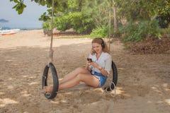 Meisjeszitting op de schommeling op het tropische strand Stock Afbeelding