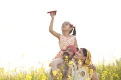 Meisjeszitting op de schouder van de vader en het werpen van document vliegtuig stock foto