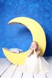 Meisjeszitting op de vloer dichtbij de maan Royalty-vrije Stock Afbeelding