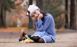 Meisjeszitting op de vloer van een park stock afbeelding