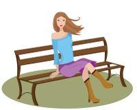 Meisjeszitting op een bank. Stock Fotografie