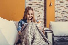Meisjeszitting op een bed met een deken en het bestuderen vóór het examen wordt behandeld dat stock afbeeldingen