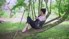 Meisjeszitting op een boom, glimlachend, gebruikend de telefoon stock videobeelden