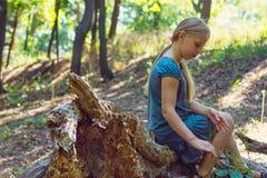 Meisjeszitting op een boomstomp stock foto