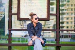 Meisjeszitting op een bushaltebank Royalty-vrije Stock Foto's