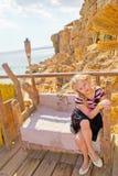 Meisjeszitting op een gesneden houten bank Royalty-vrije Stock Foto's