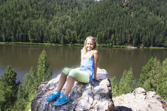 Meisjeszitting op een rots en het genieten van rivier van mening Royalty-vrije Stock Foto