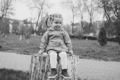 Meisjeszitting op een stomp Stock Foto
