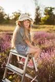 Meisjeszitting op een trapladder op feegebied van lavendel Stock Afbeeldingen