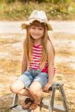 Meisjeszitting op een trapladder openlucht Jonge volwassenen Royalty-vrije Stock Afbeeldingen