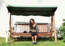 Meisjeszitting op een tuinschommeling Royalty-vrije Stock Afbeelding