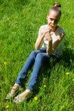 Meisjeszitting op het gras met in hand paardebloem Royalty-vrije Stock Afbeelding
