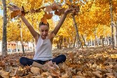 Meisjeszitting op het gras van park het spelen met droge bladeren royalty-vrije stock foto's
