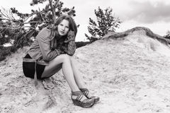 Meisjeszitting op het zand BW Stock Foto's