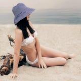 Meisjeszitting op het zand met een grote hoed Stock Foto's