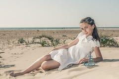 Meisjeszitting op het zand op het strand in een witte kleding stock foto