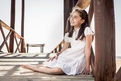 Meisjeszitting op houten vloer op het strand stock afbeeldingen