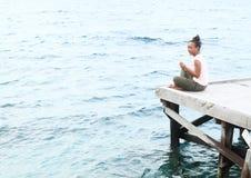 Meisjeszitting op pier door overzees royalty-vrije stock afbeeldingen