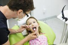 Meisjeszitting op tandstoel op haar regelmatige tandcontrole Stock Foto