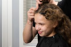 Meisjeszitting in schoonheidssalon en het glimlachen, stilist die aan haar kapsel werken royalty-vrije stock fotografie