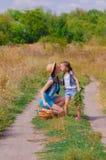 Meisjeszuster op een gebied met bloemen Royalty-vrije Stock Fotografie