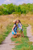 Meisjeszuster op een gebied met bloemen Royalty-vrije Stock Afbeelding